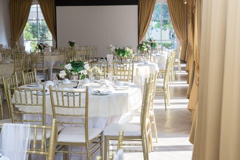 Gifta sig tabelluppsättningar i bröllopkorridor att gifta sig dekorerar förberedelsen tabelluppsättning och en annan skött om hän royaltyfri bild