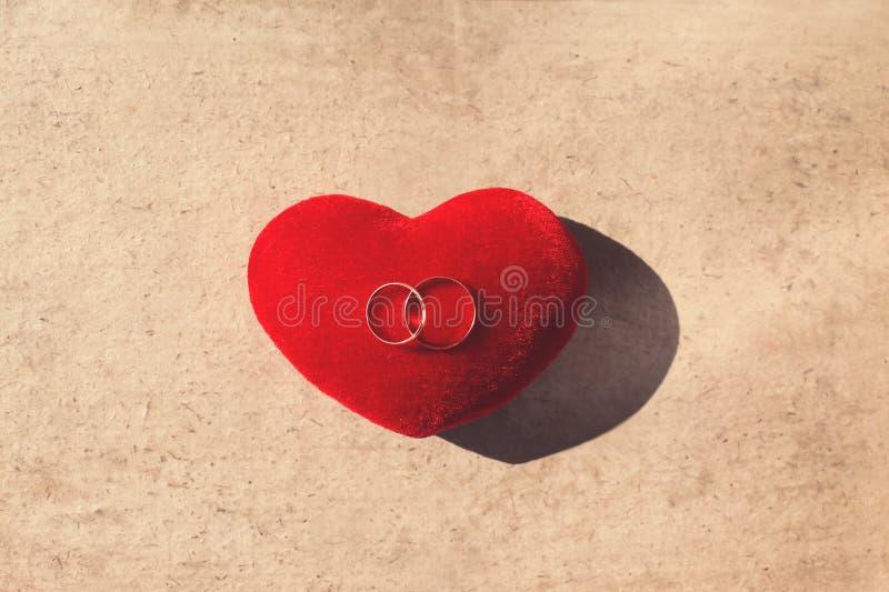 Gifta sig två guld- cirklar på en röd kuddehjärtaform över hantverket skyla över brister bakgrund fotografering för bildbyråer
