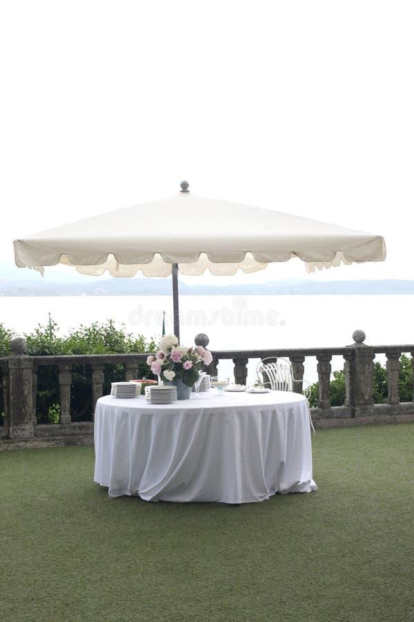 Gifta sig uppsättningen för trädgårdparti: vitt tabell- och solparaply i en elegant trädgård som är klar för partiet med kopierin royaltyfri bild