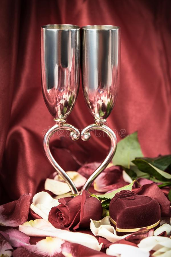 Gifta sig vinexponeringsglas och en ask med en cirkel på en festlig bakgrund royaltyfri fotografi