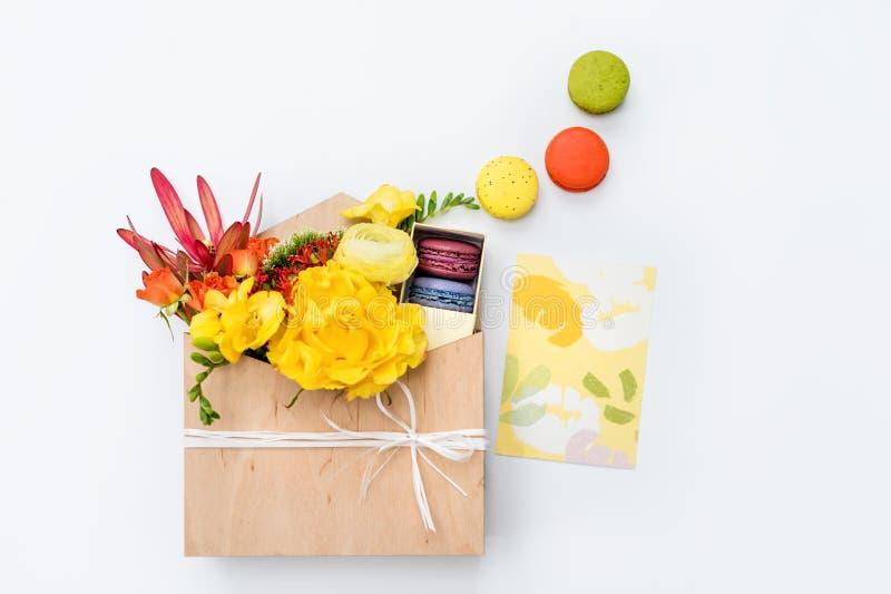 Giftbox avec des fleurs et des bonbons Macarons et bouquet de ressort dans la boîte en bois sur le fond blanc image stock