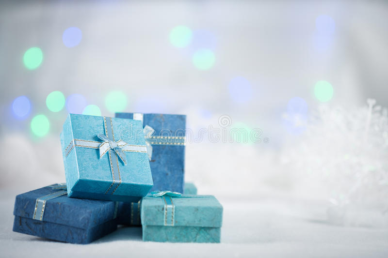 Giftbox. Blue gift boxes on the white fur on bokeh background, with copy space for season greeting. Merry Christmas or Happy New Year.AF point selection,blurred stock photos