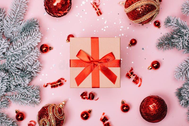 Giftbox com as bolas do Natal e o abeto vermelhos da neve no fundo pastel cor-de-rosa imagens de stock royalty free