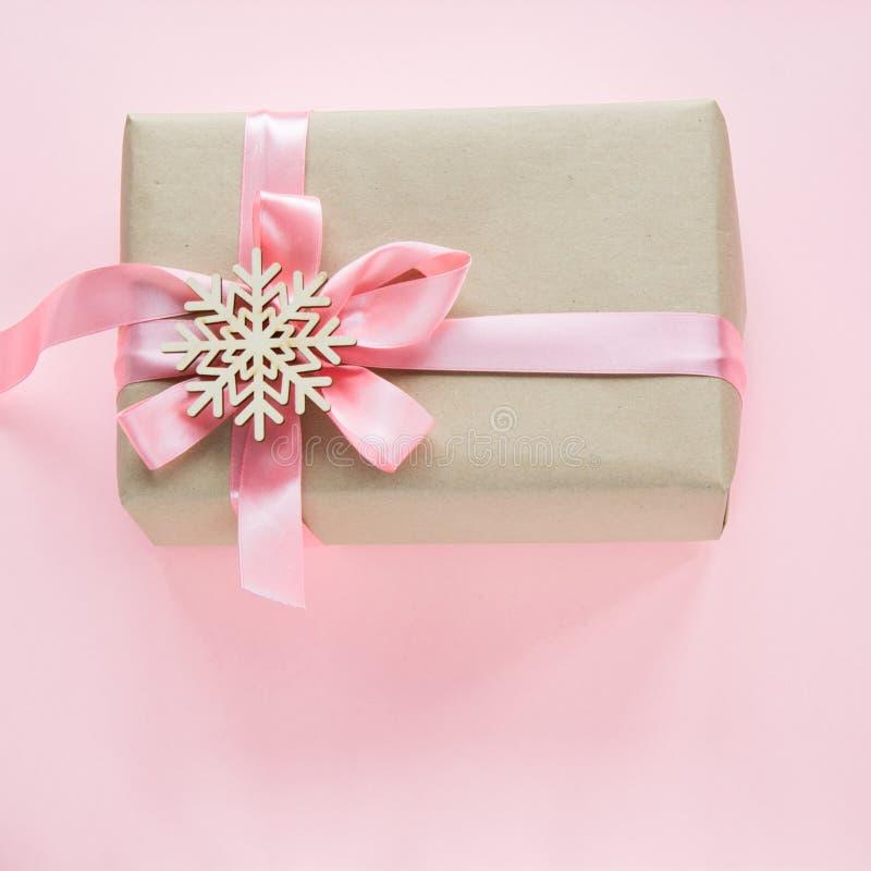 Giftbox di Natale per la ragazza con il nastro rosa ed i fiocchi di neve sul rosa immagine stock libera da diritti