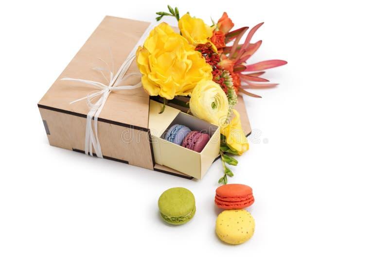 Giftbox med blommor och sötsaker Makron och vårbukett i träask på vit bakgrund arkivfoton