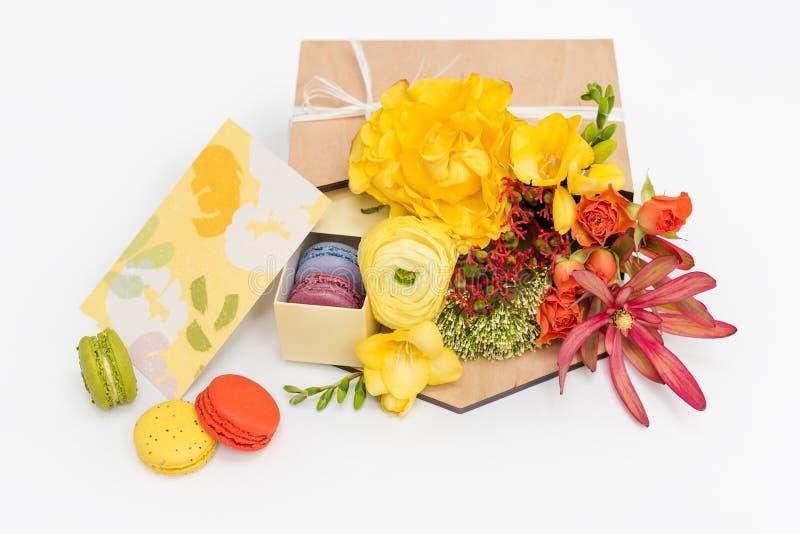 Giftbox med blommor och sötsaker Makron och vårbukett i träask på vit bakgrund arkivbild