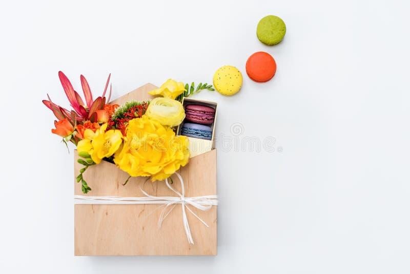 Giftbox med blommor och sötsaker Makron och vårbukett i träask på vit bakgrund fotografering för bildbyråer