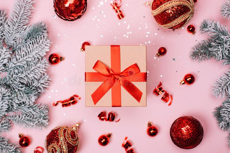 Giftbox mit roten Weihnachtsbällen und Schneetannenbaum auf rosa Pastellhintergrund lizenzfreie stockbilder