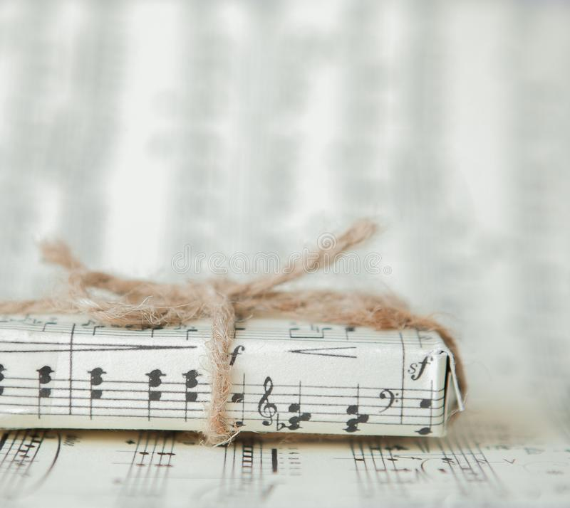 Free Giftbox On Music Sheet. A Musical Gift On Notes Background Stock Photography - 116674712