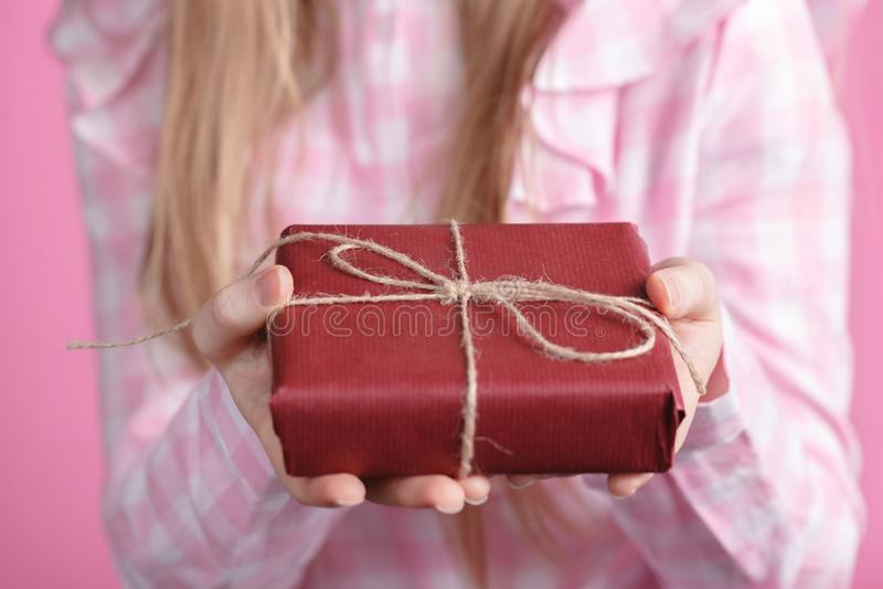 Giftbox Rad в женских руках в розовой предпосылке стоковая фотография rf