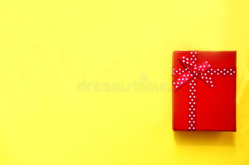 Giftbox rojo en un fondo amarillo fotos de archivo