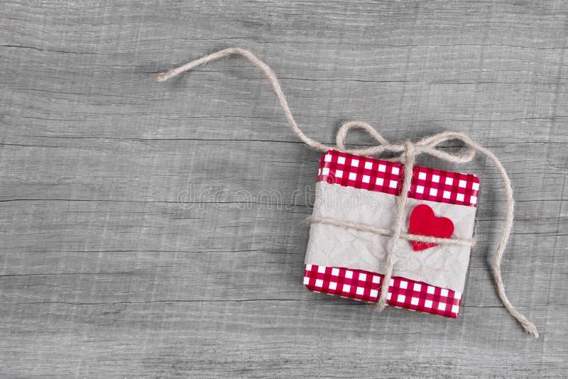 Giftbox s'est enveloppé en papier rouge avec le coeur rouge pour Noël images stock