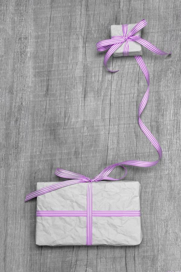 Giftboxes com a fita listrada roxa em um backround de madeira cinzento foto de stock royalty free