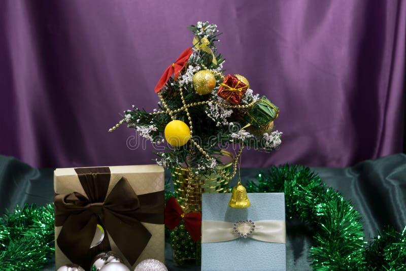 Giftboxes-, rosa und weißesweihnachtsdekorationsbälle, die an einem dekorativen weißen Weihnachtsbaum hängen Feier b des Konzept- stockbild