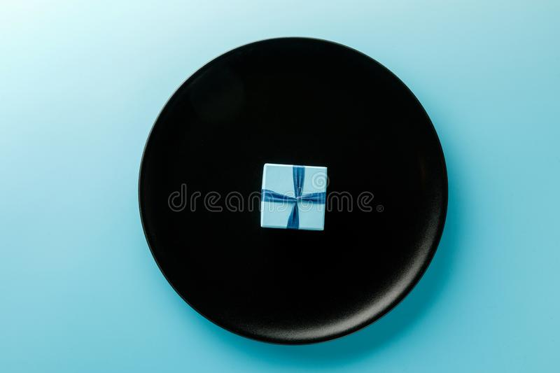 Giftdoos op een plaat op een blauwe achtergrond Het concept minimalism, manierstijl Hoogste mening, vlakke stijl stock foto's