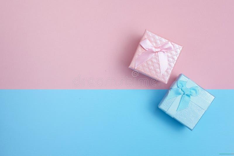 Giftdozen voor weinig jongen en meisje op roze en blauwe achtergrond Vlak leg stock fotografie
