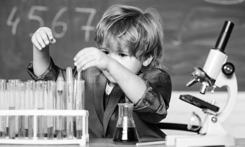 Gifted child and wunderkind. Kid study chemistry school. School education. Explore biological molecules. Toddler genius. Baby. Boy near microscope and test royalty free stock image