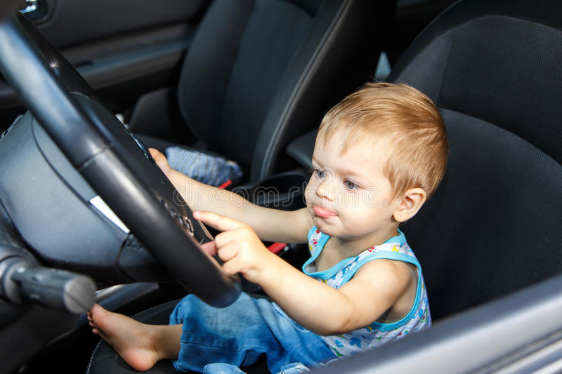 Gifted small kid drives real car. Gifted small kid with funny face drives real car stock photos