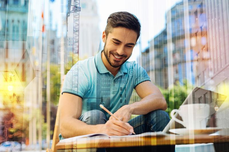 Gifted young author finishing his book and feeling excited. Young writer. Cheerful smart creative young author feeling excited and glad while sitting alone in a royalty free stock photos