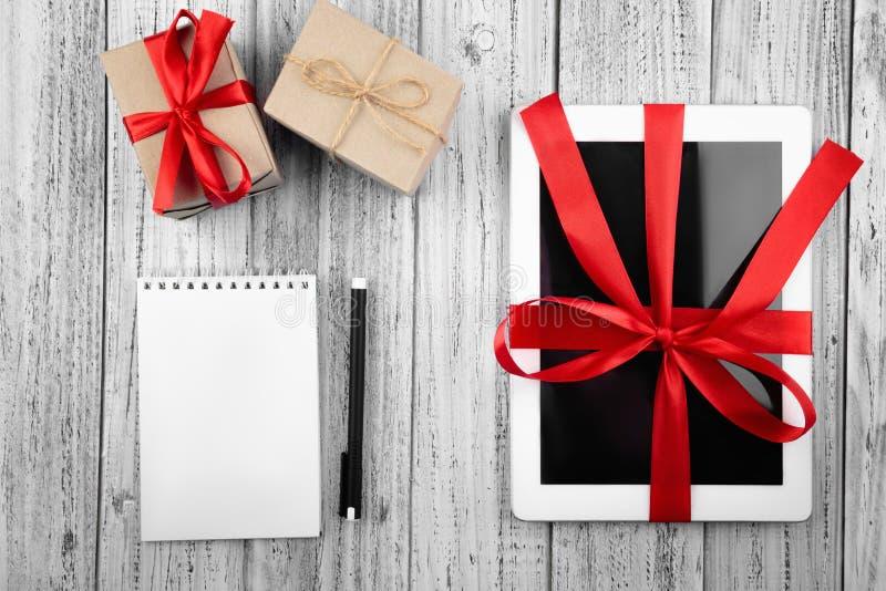 Giften en een tablet in een rood lint, een document blocnote, een pen op een witte uitstekende houten achtergrond wordt verpakt d royalty-vrije stock afbeeldingen