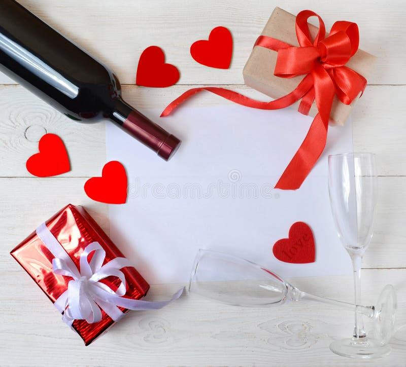 Giften, wijn, twee glazen, harten en een blad voor de tekst op taПР¾ Ð'арки, Ð ² иР½ Ð ¾, Ð'Ð ² а бР¾ каГ а, Ñ  Ð stock afbeelding