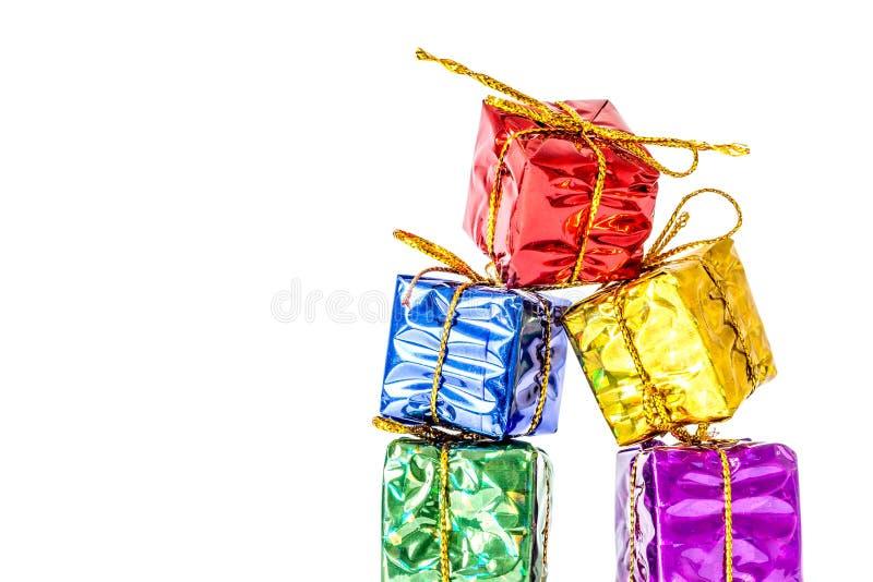 Giftendozen in een multi-colored pakket met een boogtribune wordt in een kolomclose-up op wit wordt geïsoleerd verbonden dat stock fotografie