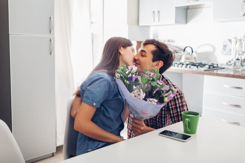Gifting bukett för ung man av blommor till hans flickvän i kök lyckligt krama för par romantisk överrrakning arkivfoton