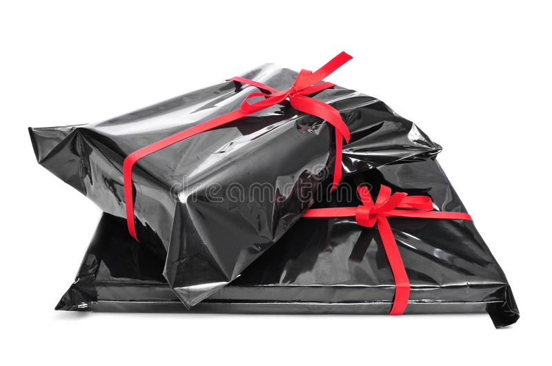 Gifts. A pile of gifts wrapped with black plastic and tied with red ribbons on a white background stock images