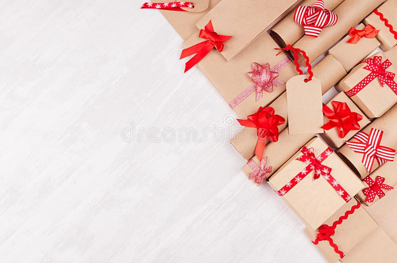 Gifts background for design advertising - set of craft paper presents with red bows, blank label on white wood board, top view. stock image