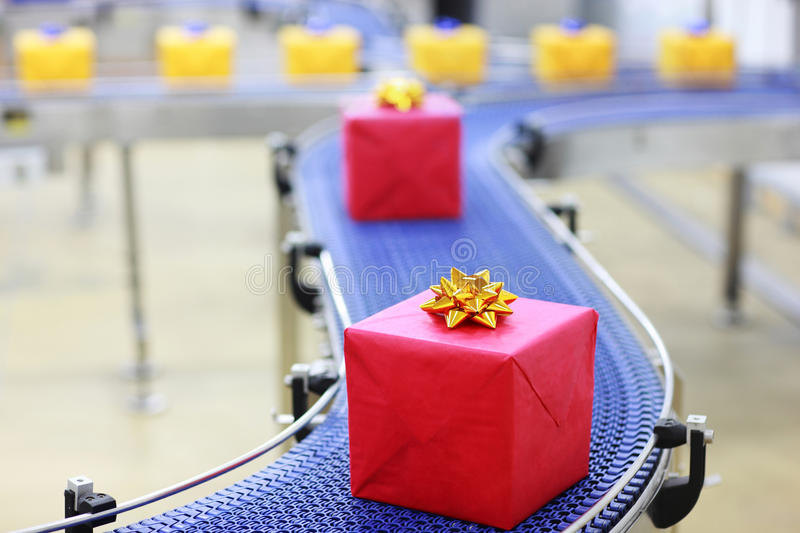 Gifts on conveyor belt in Christmas presents facto stock photography