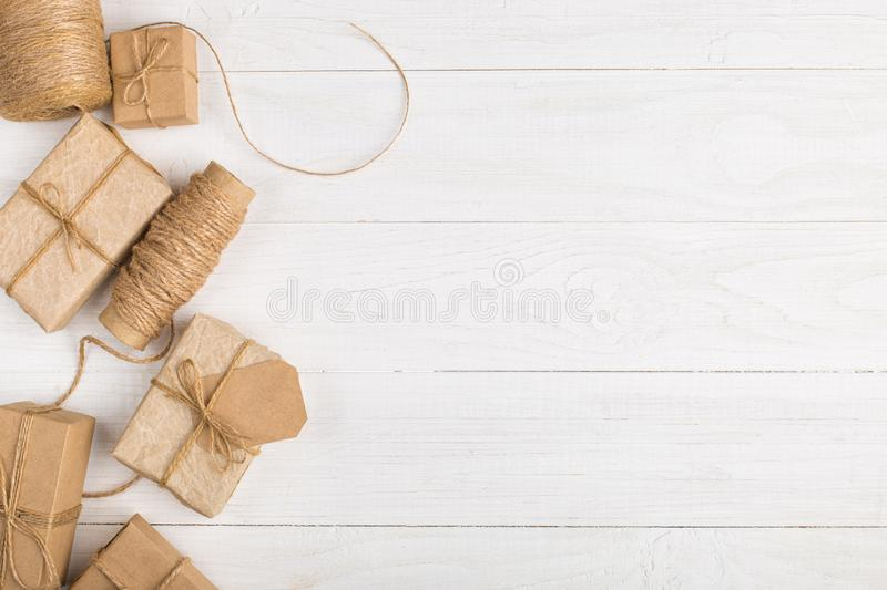 Gifts from craft paper on a white table. Christmas background, with place for text, copy space. stock photo