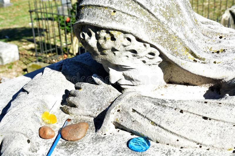 Gifts for the lady. An old tradition of leaving small gifts for the dead is practiced here for the weeping lady, a famous grave marker in West Virginia. Many stock photography