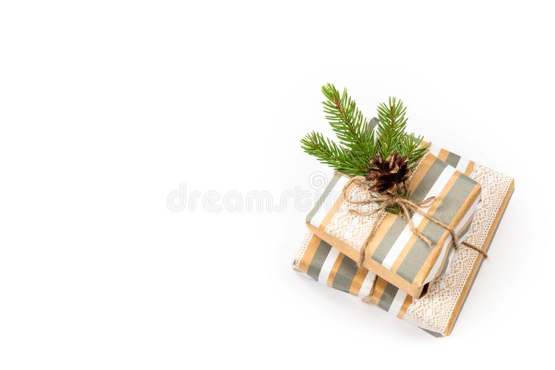 Gifts packed in craft paper on a white isolated background. Fir branches and cone. Copy space royalty free stock image