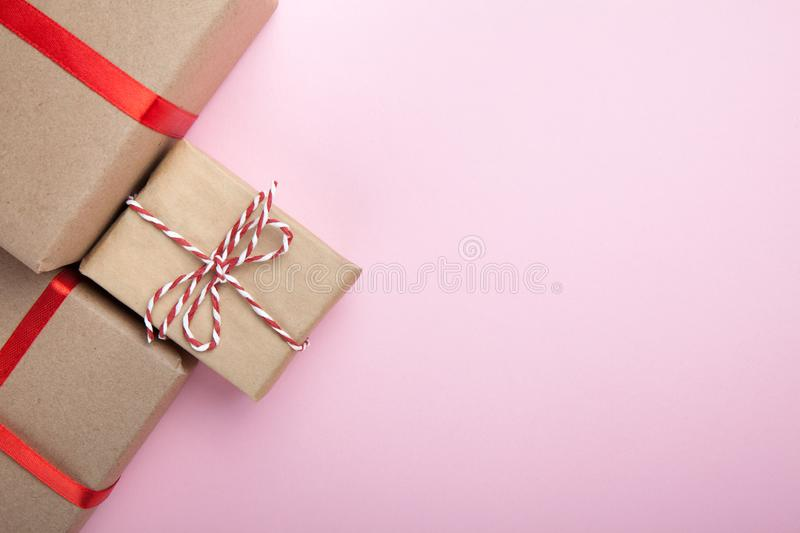 Gifts from recycled paper, decorated with red ribbons on a pink background. Copy space stock photo