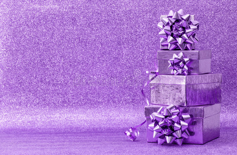 Gifts with ribbon bow on golden background. Gifts with ribbon bow on bright background. Violet holidays decoration royalty free stock photo