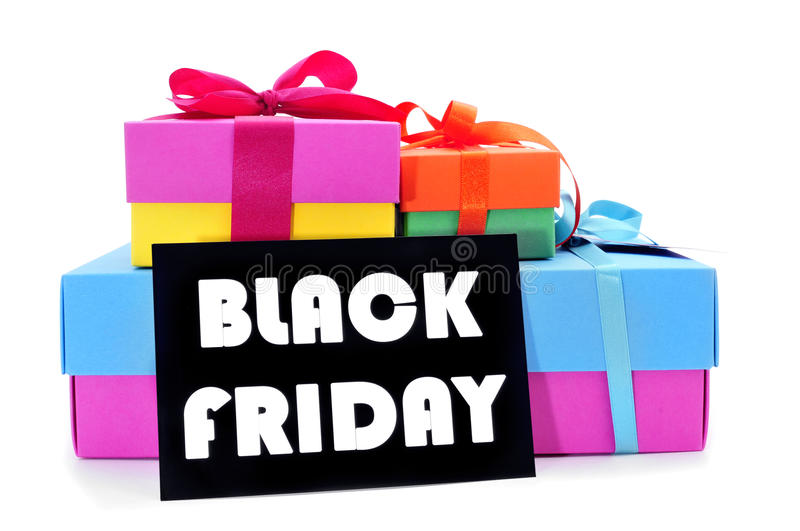Gifts and a signboard with the text black friday. A pile of gift boxes of different colors and a black signboard with the text black friday written in white, on stock images