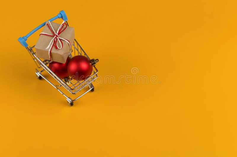 Gifts in a small shopping trolley on a yellow background, concept, copy space stock photo
