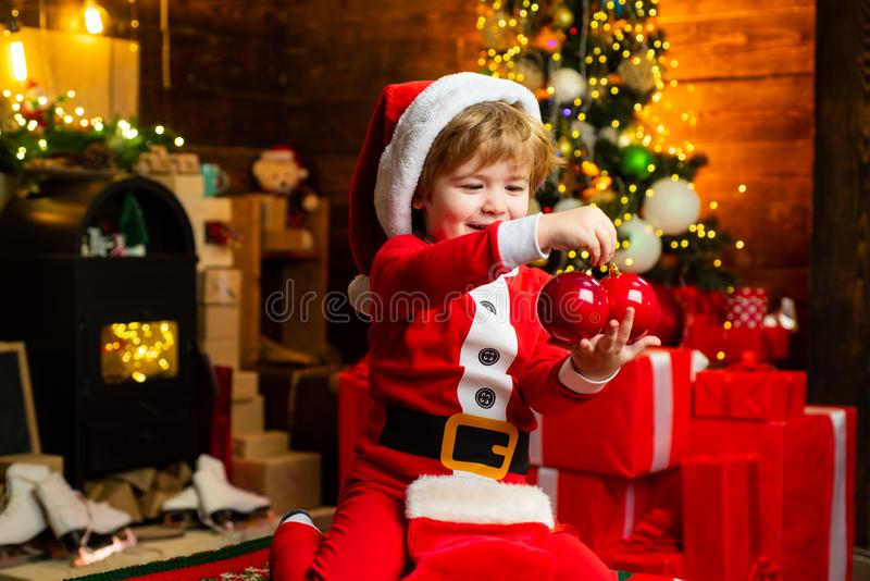 Gifts for winter holidays at fire place. Little boy with Christmas presents. Joy and happiness. Childhood moments. Child royalty free stock photos