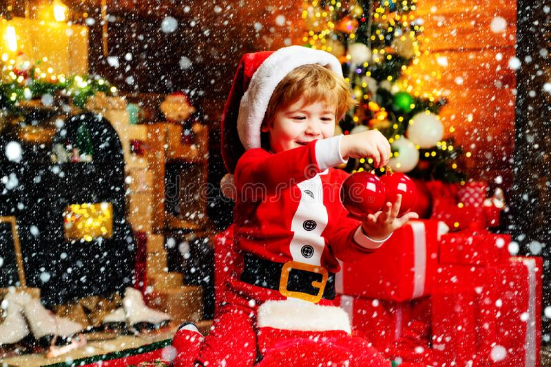 Gifts for winter holidays at fire place. Little boy with Christmas presents. Joy and happiness. Childhood moments. Child stock photos