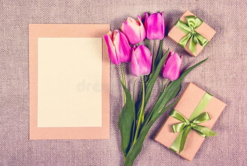 Giftvakje en brief Roze tulpen met leeg bladdocument De kaartmalplaatje van de groet royalty-vrije stock afbeelding
