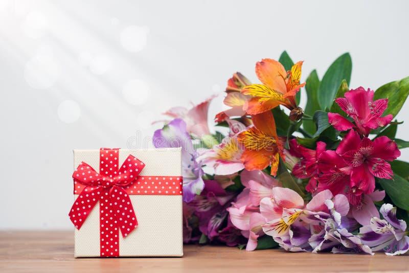 Giftvakje met de lentebloemen op houten lijst, witte achtergrond royalty-vrije stock afbeeldingen