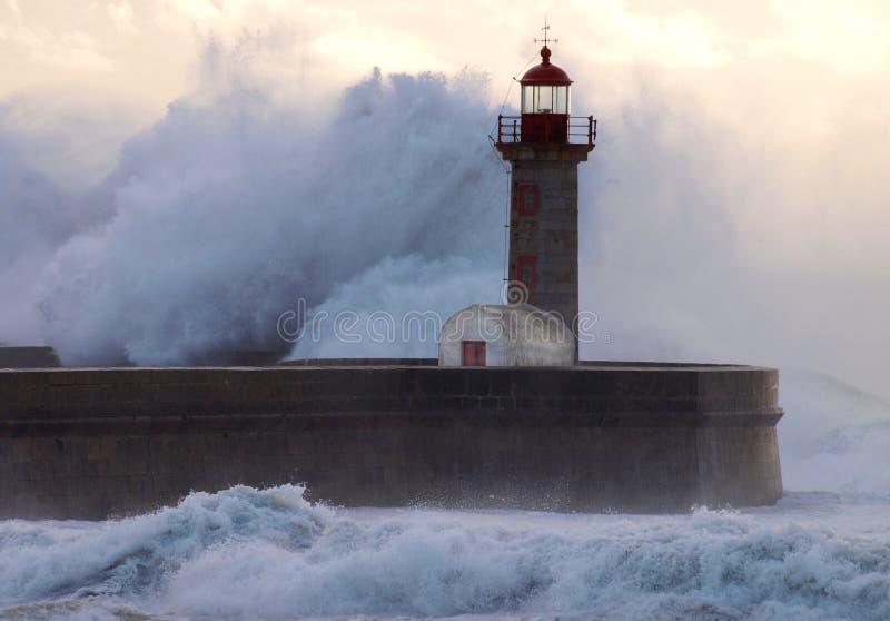 Gigant fala prawie pokrywy latarnia morska obrazy stock