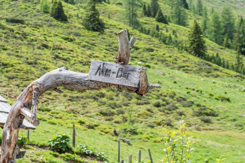 Giganta kamienny głaz na paśniku i niszczący drewniany ogrodzenie, AustriaWooden znak z wpisowym Alm barem obrazy royalty free
