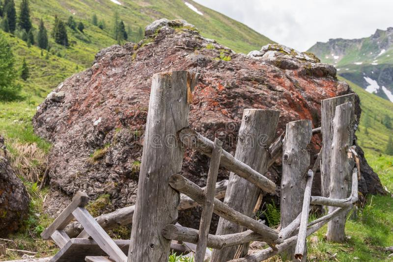 Giganta kamienny głaz na paśniku niszczącym drewnianym ogrodzeniu i, Austria zdjęcia stock