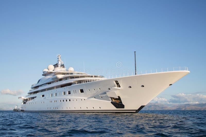 Gigantic big and large luxury mega or super motor yacht on the o. Gigantic big and large luxury mega or super motor yacht on the blue ocean royalty free stock image