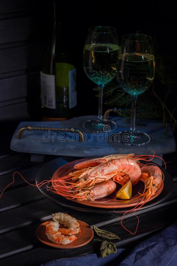 Gigantyczna garnela, cytryna, dwa szkła biały wino Jaskrawa fotografia na czarnym tle zdjęcie royalty free