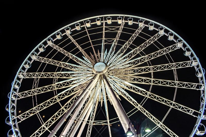 Gigantyczny ferris koło przy nocą zaświecał up z białym i żółtym światłem zdjęcia royalty free