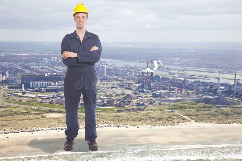Gigantyczny młody pracownik z stalową fabryką zdjęcia stock
