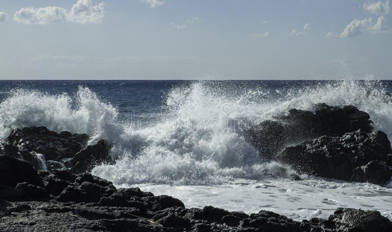 Gigantyczny Turkusowy pęcznienie rozbija w czarne lawowe falezy na niebieskie niebo letnim dniu w Sicily zdjęcia stock