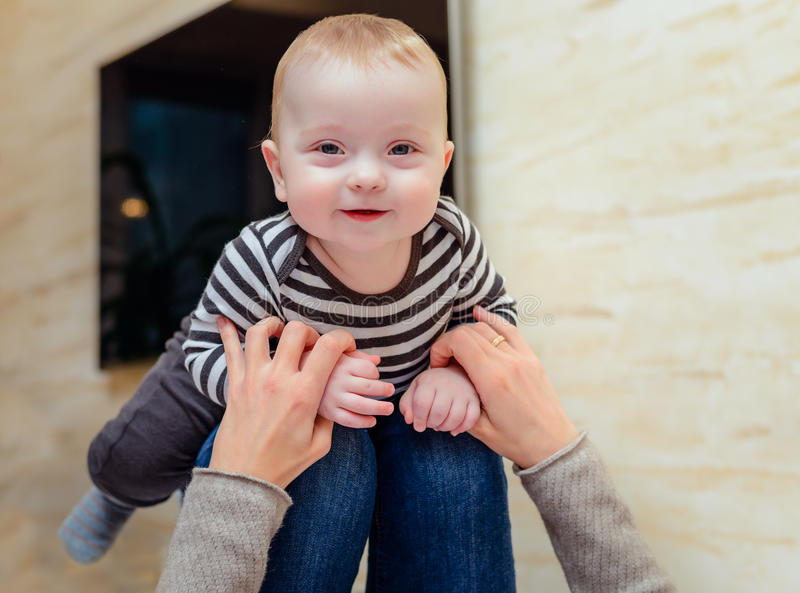 Giggling baby up on knees of adult royalty free stock photography
